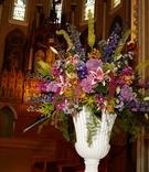 ceremony flower arrangement with stargazer lilies, stocks, bright colors, white vase