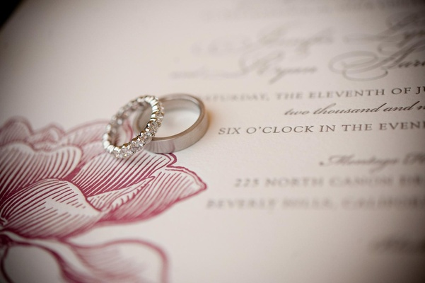 Platinum wedding rings on pink wedding invitation