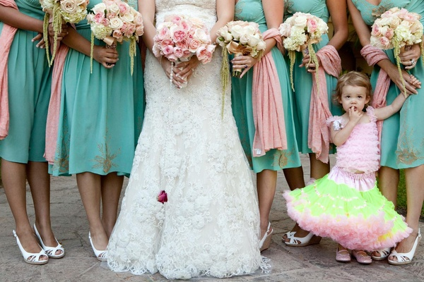Bottom half of bridesmaids with flower girl in festive dress