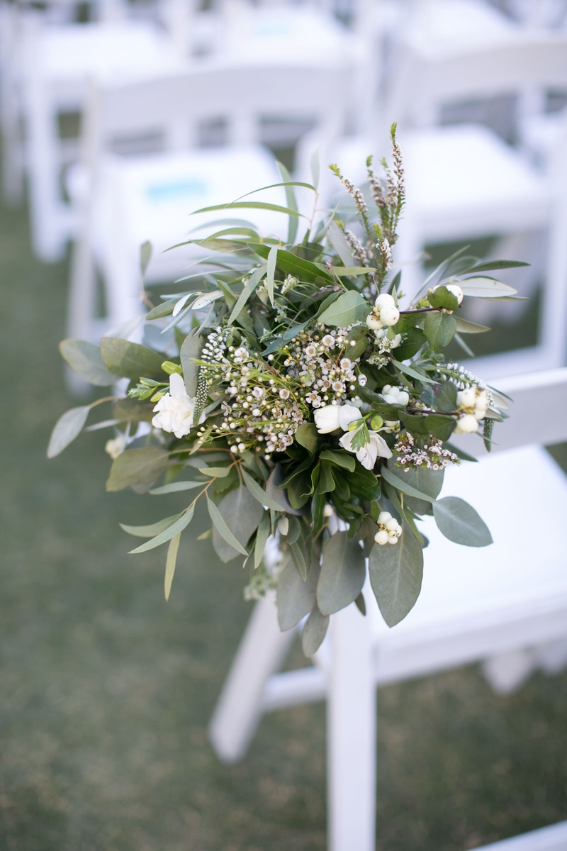 ceremony chair decoration with leaves and small white flowers