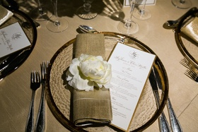 Gold-rim charger with white peony at wedding reception