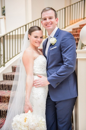 Bride in strapless beaded wedding dress with hair pulled back and veil groom in navy blue suit