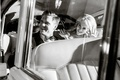 Black and white photo of the newlywed couple waves goodbye to guests from their classic getaway car