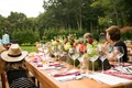Wedding shower guests at wooden table with flower runner