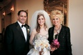 Bride in regal wedding dress with mom and dad