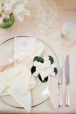 wedding place setting with clear charger place, cream napkin tied with blush, gardenia bloom on side