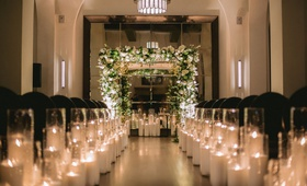wedding ceremony hotel figueroa candles along aisle black guest chairs greenery white flower chuppah