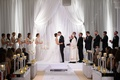 bridal party applauds during bride and groom's first kiss white wedding ceremony altar