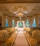 Wedding ceremony custom white and gold border aisle runner ballroom ornate white flowers gold chairs