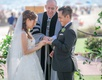 groom grins widely while bride and groom exchange rings during wedding ceremony