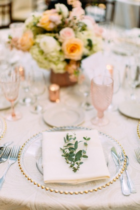 wedding reception gold bead charger plate pink glassware goblet orange pink flowers greenery