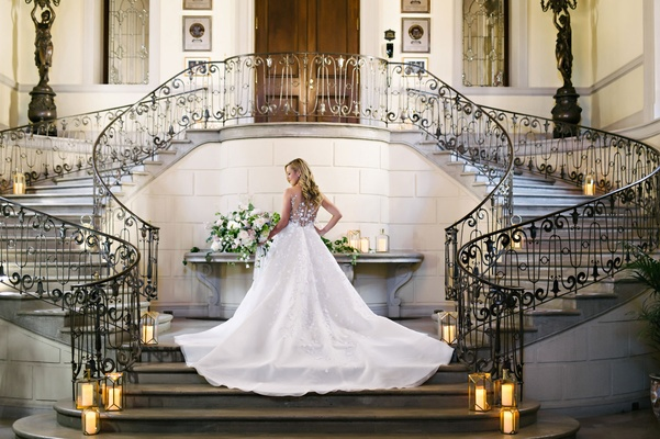 Back of Angel Sanchez wedding dress in grand stairway at Oheka Castle