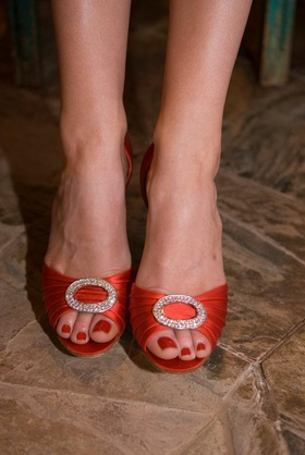Red pedicure and red wedding heels with rhinestone buckle