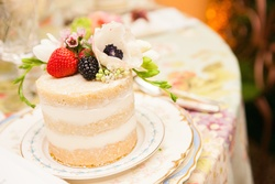 Three layer sponge cake with berry topping and anemone flower