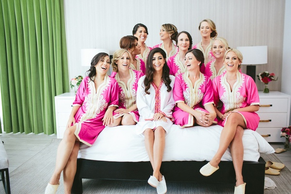 fuchsia and gold robes, white and red robe bride and bridesmaids on bed