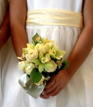 Flower girl holds bouquet of orchid and rose flowers