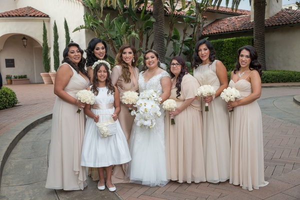 Bride in wedding dress orchid bouquet bridesmaids in tan taupe champagne mismatched dresses