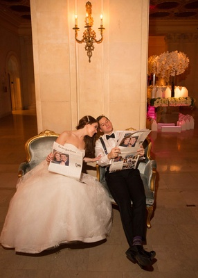 Bride in strapless wedding dress groom in bow tie suspenders reading special edition of The Times
