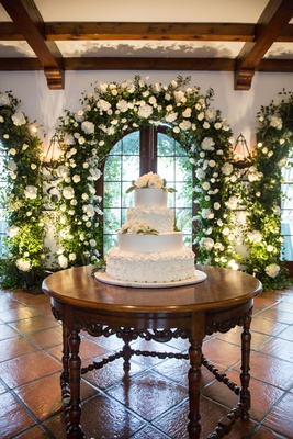 white wedding cake with fresh flowers on spanish tile wood table greenery archway wood beams