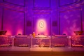 pink and purple uplighting behind ice bar with couples initials at wedding reception