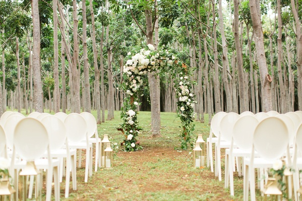 Forest wedding ceremony green arch neutral flowers white chairs and lanterns on aisle