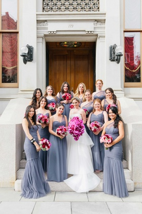 Bridesmaids in one shoulder Amsale mismatch mermaid bridesmaid dresses with pink and purple bouquets