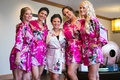 a bride in a light pink robe with floral decorations posing with four bridesmaids hot pink robes