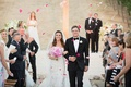 Wedding guests toss pink petals on newlyweds