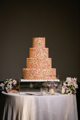 wedding cake rainbow sprinkles four layer round tier modern cake on mirror stand