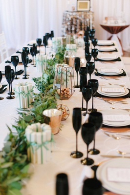 a unique reception tablescape with black glassware copper chargers and utensils and a green runner