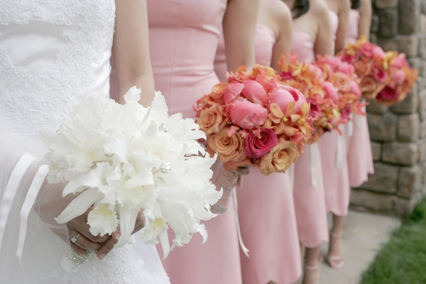 Bride with a bouquet of white flowers and bridesmaids with bouquets of pink and orange flowers