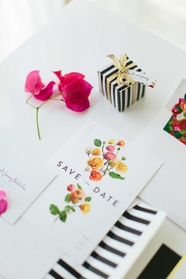 black, white, and gold save-the-date cards with colorful flowers black white stripes
