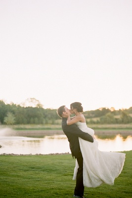 Groom in black suit lifts and kisses bride in a lace dress on a green lawn by the water