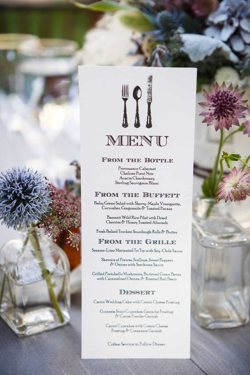 rustic menu with fork knife spoon on outdoor reception table with wildflowers in small vessels