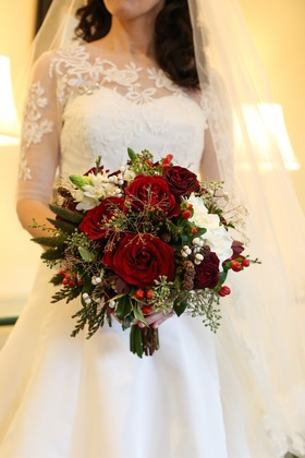 Red and green wedding bouquet with miniature pinecones, greenery, and red berries