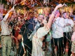 bride and groom celebrating with guests as colorful metallic streamers fall down