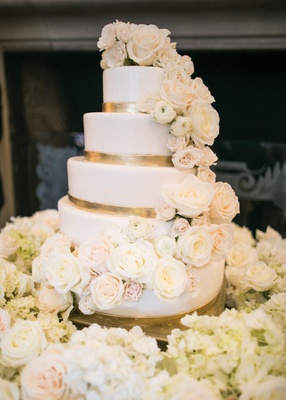 five-tiered wedding cake with ivory and blush roses and gold painted trim