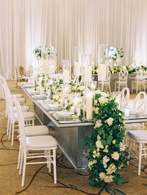 Wedding reception mirror long table with white chairs candles and flower greenery runner overflowing