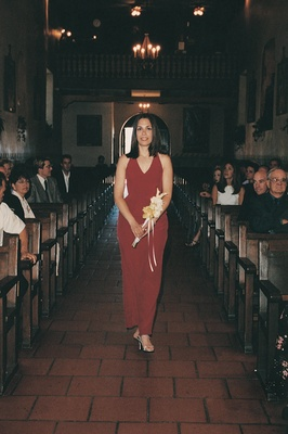 Bridesmaid wearing cherry gown down aisle