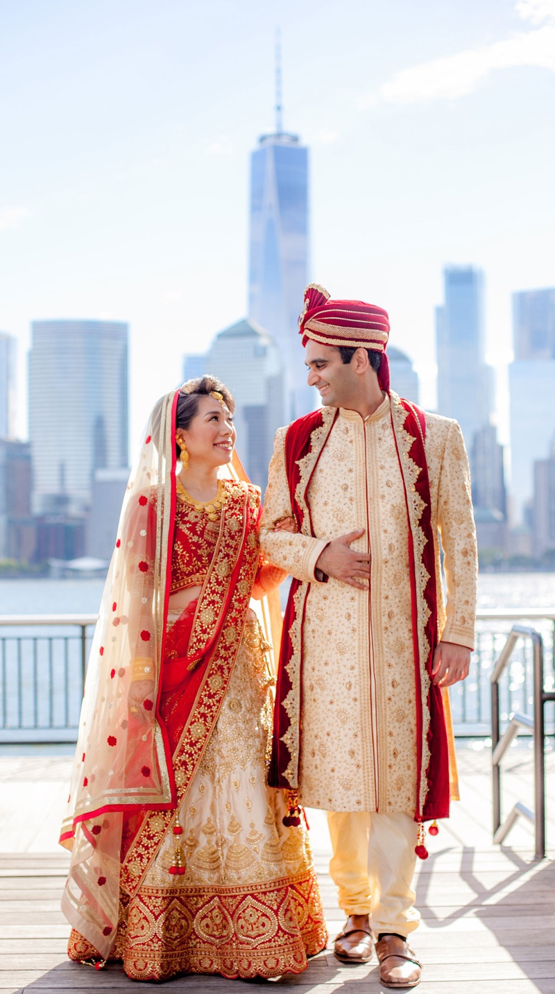 bride in red and gold traditional wedding attire for indian ceremony groom with view of new york
