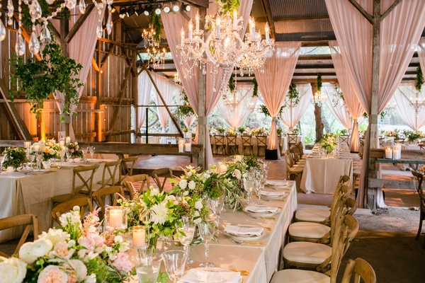 Barn wedding venue blush drapes low centerpieces long tables wood chairs chandeliers