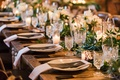 Long wood table with greenery runner cut vintage glassware napkin greens vines reception table