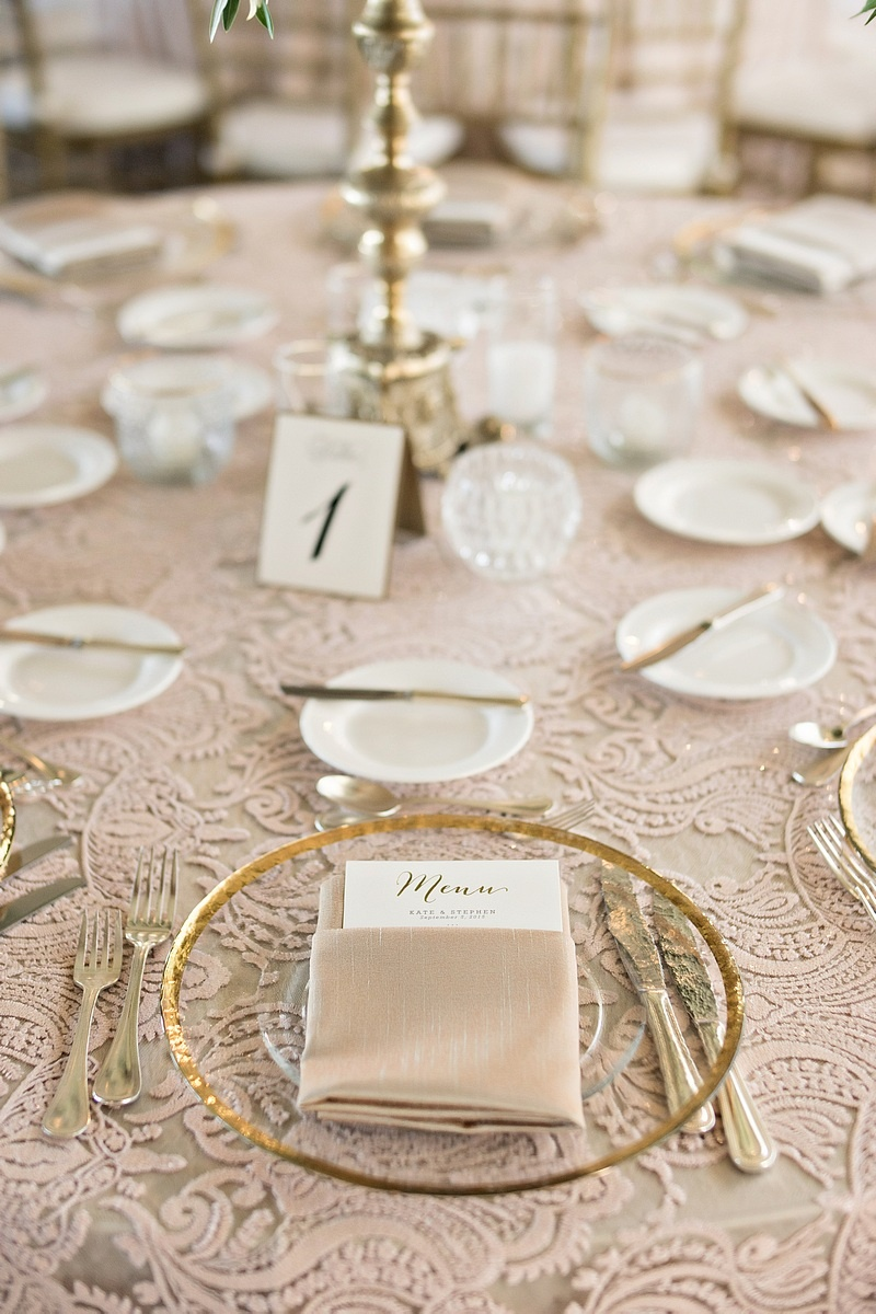 gold-rimmed glass chargers, gold flatware, blush linens