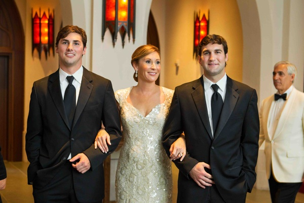 Two groomsmen escorting mother of bride down aisle