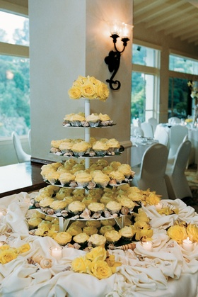 Yellow cupcakes on tiers next to sea shells