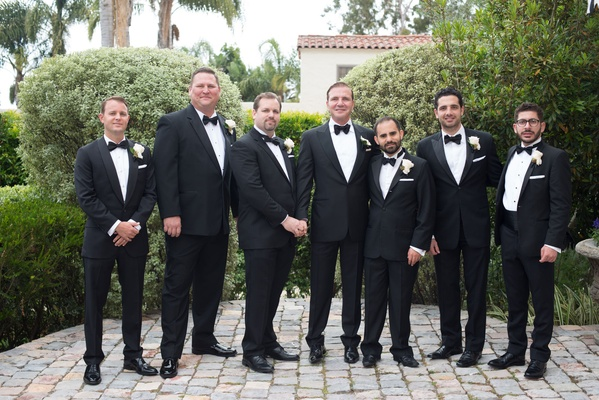 Same sex wedding friends and family all men with boutonnieres tuxedos