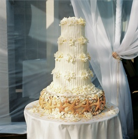 White wedding cake with seashell cake stand