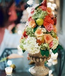 Stone urn filled with rose and hydrangea flowers and apple and pear fruits