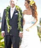 Newlyweds smile at ceremony in Hawaii with leis