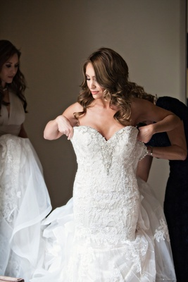 bride helped into kittychen couture lace gown with beading along sweetheart neckline